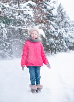 A little girl in a bright jacket plays in the winter snowy forest.