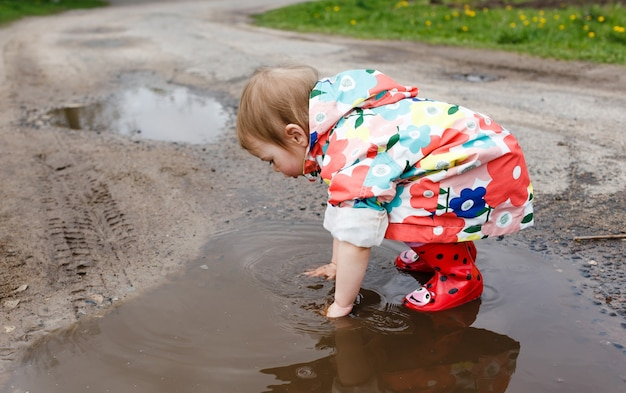 A little girl in a bright jacket and rubber boots happily plays in a spring puddle. children's happiness.