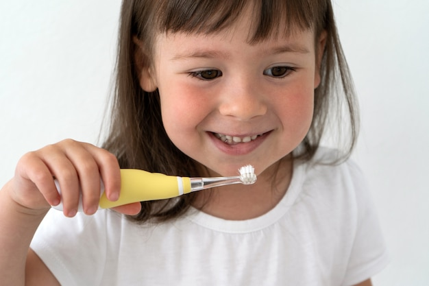 Little girl brushes her teeth herself