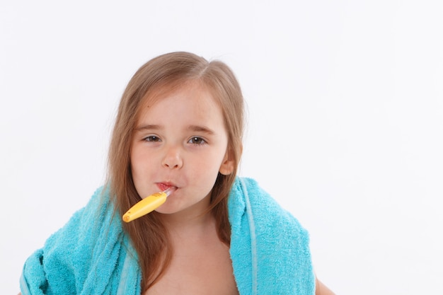 A little girl brushes her teeth on a white background. portrait of a child with a yellow toothbrush. blue towel around her neck. morning hygiene procedures