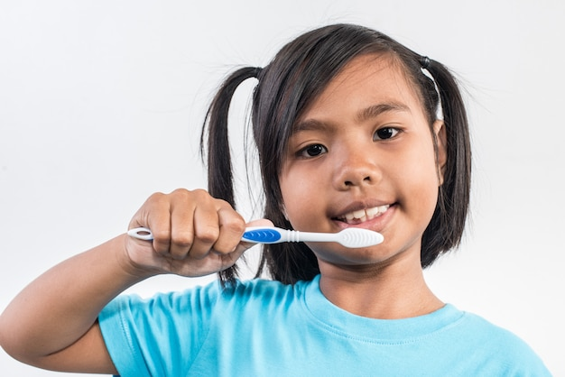 Little girl brushing her teeth in studio shot