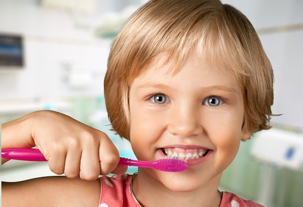 Little girl brushing teeth isolated on white