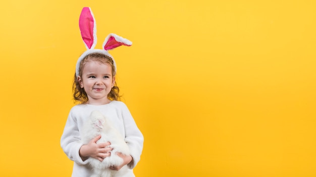 Little girl in bunny ears standing with rabbit