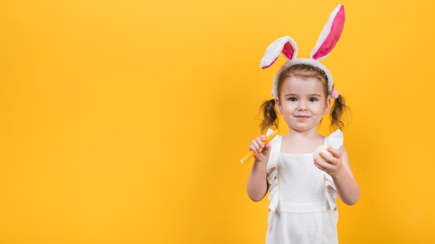Little girl in bunny ears with egg and felt pen