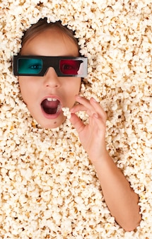 Little girl buried in popcorn wearing 3d glasses