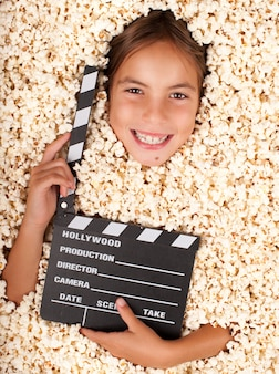 Little girl buried in popcorn with movie clapper board