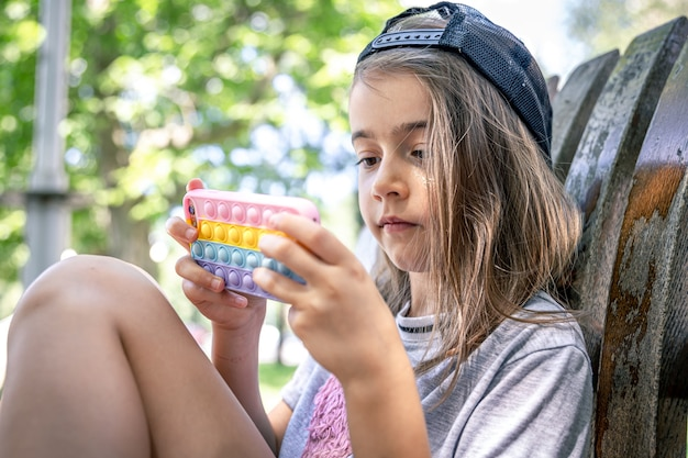 Little girl in a cap with a smartphone in a case in the style of toys anti stress pop it.