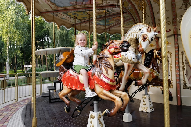 Little girl on the carousel in the summer