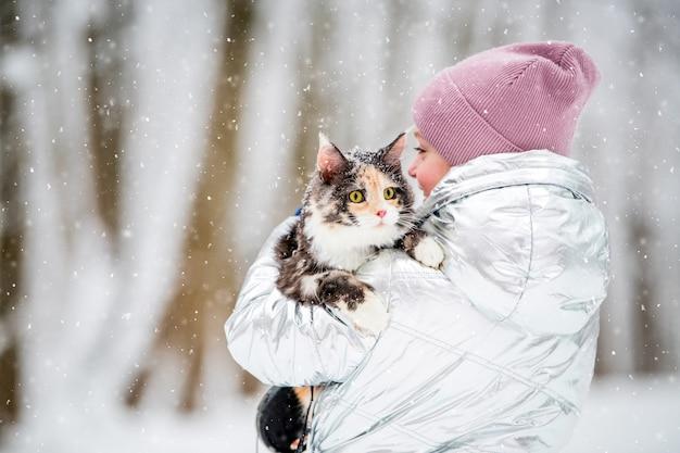 雪の降る冬に少女が猫を腕に抱く