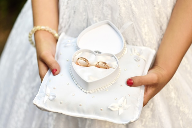 A little girl carries wedding rings on a cushion in a heart-shaped box