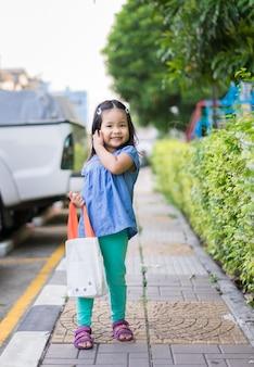 買い物をするための布袋を持っている少女