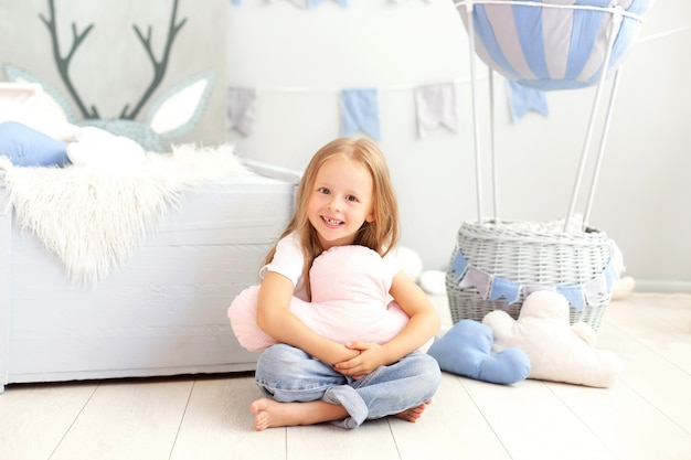 A little girl in casual clothes holds a cloud pillow against the wall of a decorative balloon. the child plays in children room. the concept of childhood, travel. birthday, holiday decorations