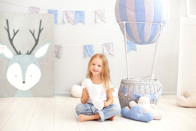 A little girl in casual clothes holds a cloud pillow against the wall of a decorative balloon. the child plays in the children's room. the concept of childhood. birthday, holiday decorations