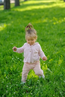 Little girl in casual clothes makes her first steps on the grass