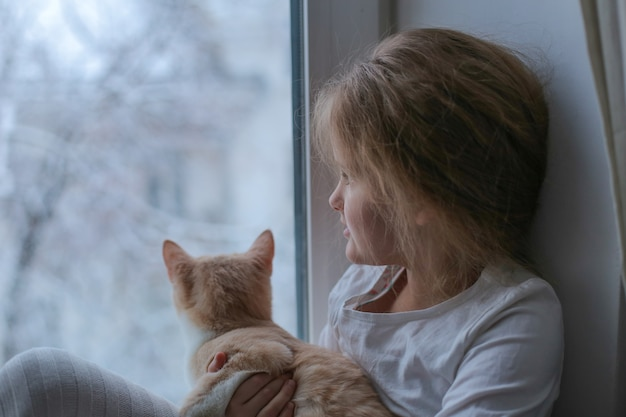 Little girl and cat are sitting on the windowsill and looking out the window