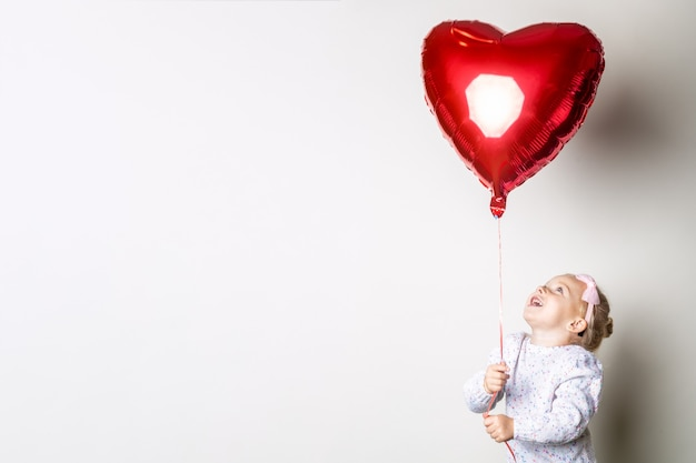 Little girl catches a heart air balloon on a light background. concept for valentine's day, birthday. banner.