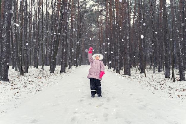 Маленькая девочка ловит снежинки в снегопаде в зимнем парке