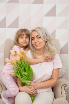Little girl of caucasian appearance congratulate mother on mother's day and give a bouquet of flowers and a card in a bright living room in a scandinavian style