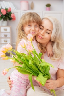 Little girl of caucasian appearance congratulate mother on mother's day , tenderly hugs her mother, and give a bouquet of flowers in a bright living room in a scandinavian style