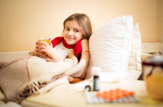 어린 소녀가 독감에 걸리고 침대에서 레몬과 함께 뜨거운 차를 마시는