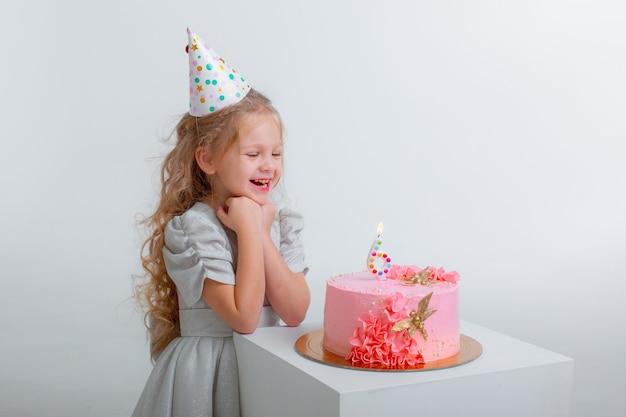 Маленькая девочка отмечает свой день рождения, задувая свечи на торте