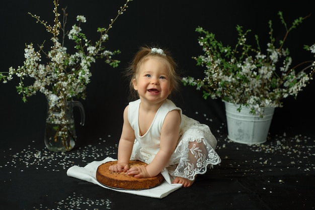 Little girl celebrates her first birthday. girl eating her first cake.