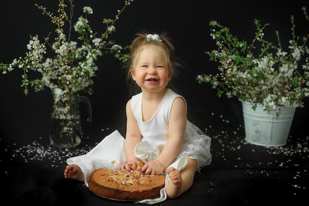 어린 소녀는 그녀의 첫 생일을 축하합니다. 그녀의 첫 케이크를 먹는 여자.