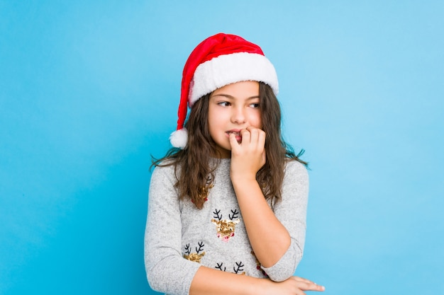 Little girl celebrating christmas day biting fingernails, nervous and very anxious.