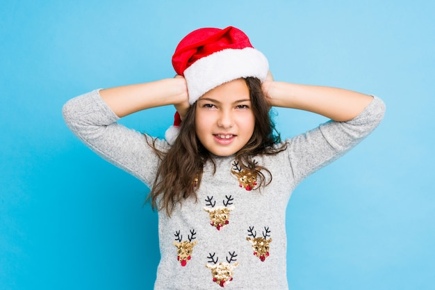 Little girl celebrating christmas day covering ears with hands trying not to hear too loud sound.