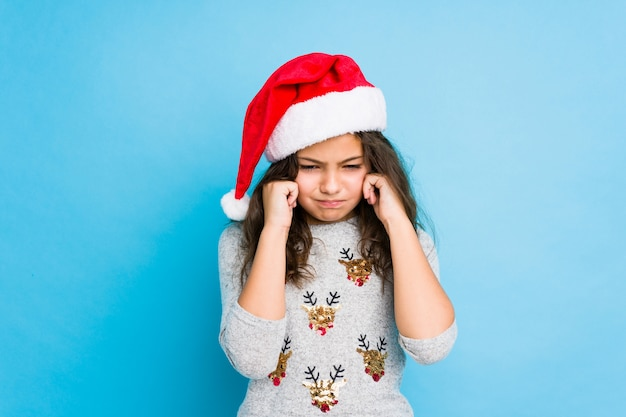 Little girl celebrating christmas day covering ears with hands.