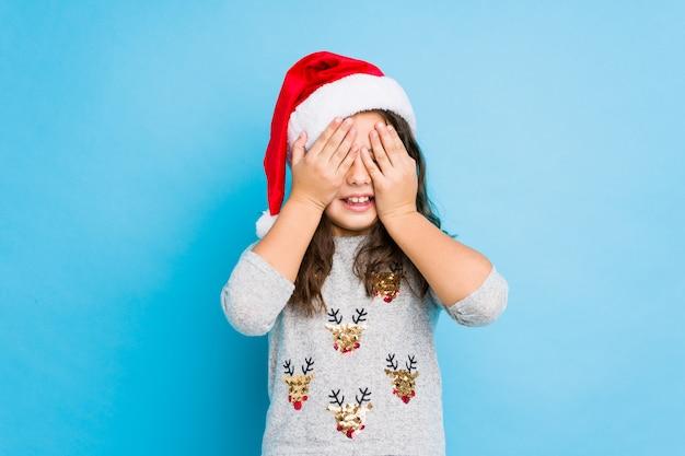 クリスマスの日を祝っている少女は、目を覆って、驚きを広く待っている笑顔です。