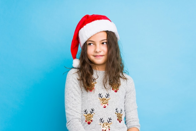 Little girl celebrating christmas day dreaming of achieving goals and purposes
