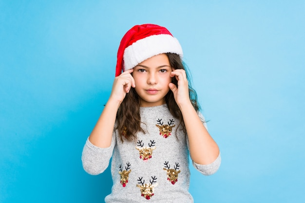 Little girl celebrating christmas day focused on a task, keeping forefingers pointing head.
