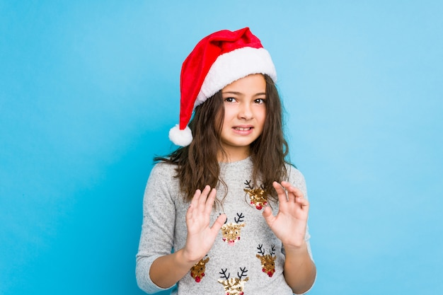 Little girl celebrating christmas day rejecting someone showing a gesture of disgust.