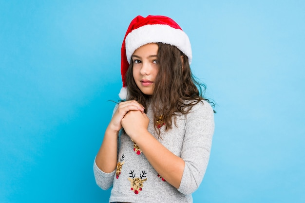 Little girl celebrating christmas day scared and afraid.
