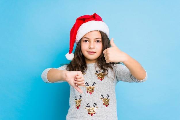 Маленькая девочка празднует рождество показывает палец вверх и вниз, трудно выбрать концепцию