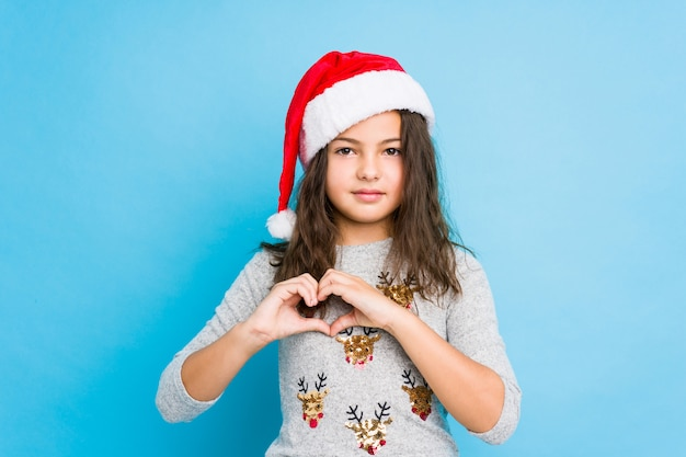 Little girl celebrating christmas day smiling and showing a heart shape with hands.