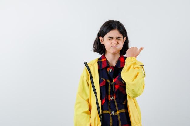 Bambina in camicia a quadri, giacca che soffia sulle guance e sembra divertente, vista frontale.