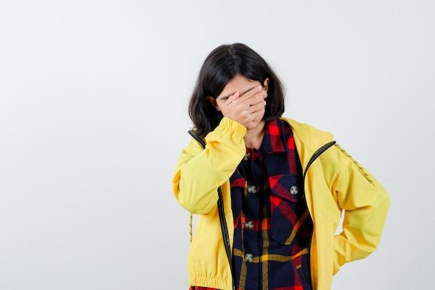 Bambina in camicia a quadri, giacca che copre gli occhi con la mano e sembra smemorata, vista frontale.
