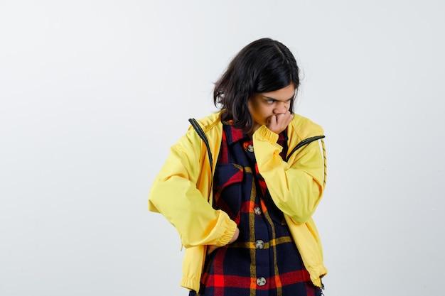 Bambina in camicia a quadri, giacca che fa cuscino sulla sua mano e dall'aspetto pensieroso, vista frontale.