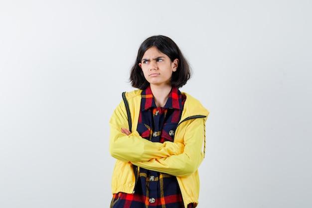 Bambina in camicia a quadri, giacca in piedi con le braccia incrociate e sguardo cupo, vista frontale.