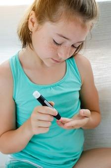 Маленькая девочка проверяет уровень сахара в крови с помощью ланцетника и глюкометра дома