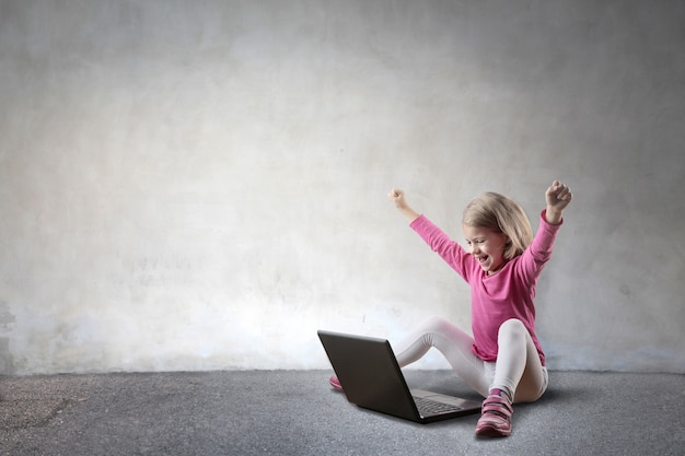 Little girl cheering and looking at a laptop