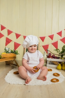 Little girl in a chef costume sits and holds a bagel