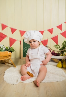 Little girl in a chef costume sits in pizzeria
