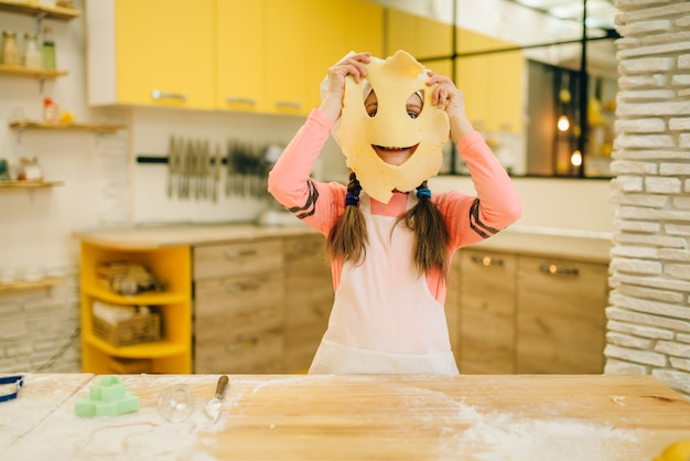 Little girl chef made a funny face out of dough