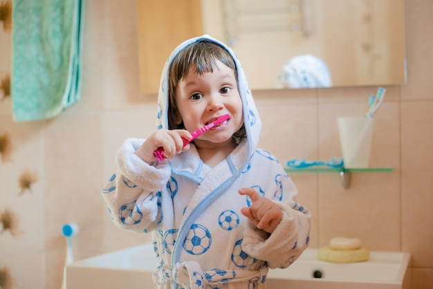 A little girl  child brushes teeth in the bathroom. hygiene of the oral cavity.