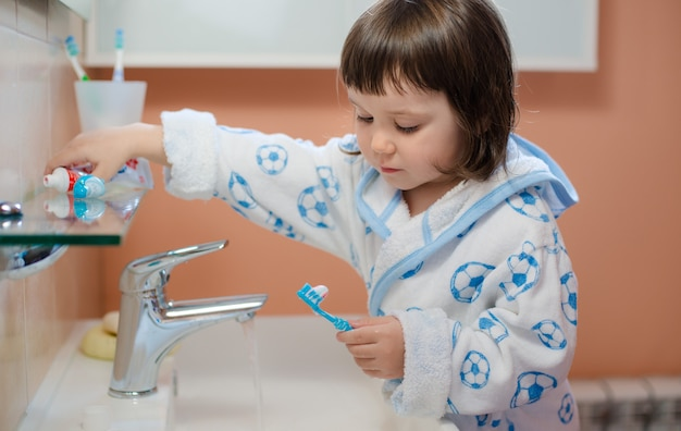 A little girl or child brushes teeth  the bathroom. hygiene of the oral cavity.