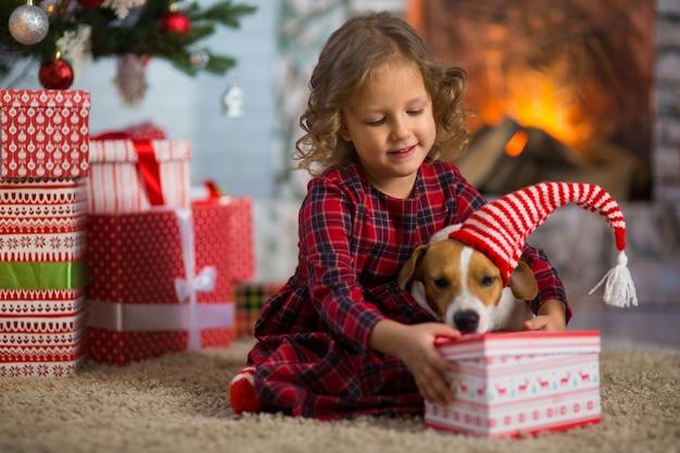 Маленькая девочка празднует рождество с собакой джек рассел терьер дома под елкой