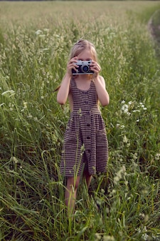 Little girl child in a checkered dress stands with a retro camera and photographs in the summer field